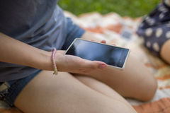 Συνεδρίαση γυναικών υπαίθρια και εκμετάλλευση ένα smartphone Στοκ εικόνες με δικαίωμα ελεύθερης χρήσης