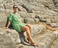 Συνεδρίαση γυναικών χαμόγελου στις καταστροφές του Colosseum Τουρκία, Kem Στοκ φωτογραφία με δικαίωμα ελεύθερης χρήσης