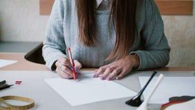 Συνεδρίαση γυναικών Brunette στον πίνακα, το μολύβι εκμετάλλευσης και το σχεδιάγραμμα σχεδίων σε χαρτί Σβήστε στο σκίτσο ολισθαίν απόθεμα βίντεο
