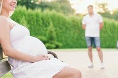 Συνεδρίαση εγκύων γυναικών στον πάγκο, άτομο που εξετάζει την Στοκ Φωτογραφία
