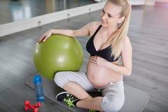 Συνεδρίαση εγκύων γυναικών χαμόγελου στο χαλί γυμναστικής με τη σφαίρα pilates Στοκ Εικόνα