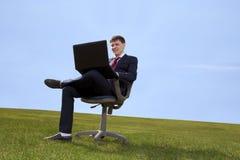 Συνεδρίαση επιχειρηματιών στην καρέκλα με ένα lap-top στο πράσινο λιβάδι Στοκ φωτογραφία με δικαίωμα ελεύθερης χρήσης