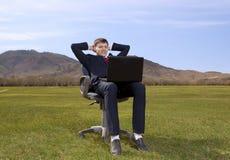 Συνεδρίαση επιχειρηματιών στην καρέκλα με ένα lap-top στο πράσινο λιβάδι Στοκ εικόνες με δικαίωμα ελεύθερης χρήσης