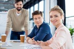 Συνεδρίαση επιχειρηματιών στον πίνακα με τους συναδέλφους στην επιχειρησιακή συνεδρίαση Στοκ Εικόνες