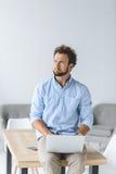 Συνεδρίαση επιχειρηματιών στον πίνακα με το lap-top στα γόνατα στην αρχή Στοκ εικόνα με δικαίωμα ελεύθερης χρήσης