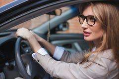 Συνεδρίαση επιχειρηματιών στο αυτοκίνητό της Ξανθός με μακρυμάλλη και στα γυαλιά Στοκ εικόνες με δικαίωμα ελεύθερης χρήσης