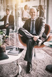 Συνεδρίαση επιχειρηματιών χαμόγελου στην καρέκλα στην αρχή Στοκ φωτογραφία με δικαίωμα ελεύθερης χρήσης