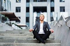 Συνεδρίαση επιχειρηματιών Oung στα βήματα του γραφείου και meditates Στοκ εικόνα με δικαίωμα ελεύθερης χρήσης