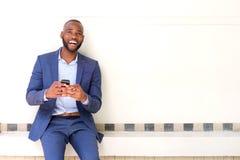 Συνεδρίαση επιχειρησιακών ατόμων χαμόγελου αφρικανική ενάντια στον τοίχο με το κινητό τηλέφωνο Στοκ φωτογραφία με δικαίωμα ελεύθερης χρήσης