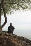 Συνεδρίαση εφήβων στο κούτσουρο και σκέψη Στοκ Εικόνες