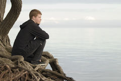 Συνεδρίαση εφήβων στο κούτσουρο και σκέψη Στοκ Φωτογραφία