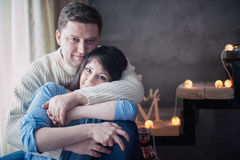 Συνεδρίαση ζευγών αγάπης που αγκαλιάζει στη σκάλα που διακοσμείται με τη γιρλάντα Χριστουγέννων Στοκ εικόνες με δικαίωμα ελεύθερης χρήσης