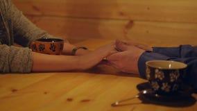 Συνεδρίαση ζευγών αγάπης σε έναν καφέ Το άτομο αγγίζει ήπια τη φίλη χεριών Κλείστε να παρουσιάσει χέρια του νέων αρσενικού και το απόθεμα βίντεο