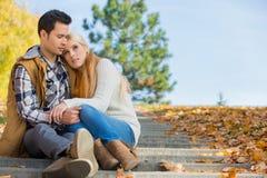 Συνεδρίαση ζευγών αγάπης στα βήματα πάρκων Στοκ εικόνα με δικαίωμα ελεύθερης χρήσης