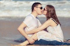 Συνεδρίαση ζευγών αγάπης στην παραλία στο χρόνο ημέρας Στοκ Εικόνες