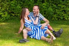 Συνεδρίαση ζευγών αγάπης στη χλόη Στοκ εικόνες με δικαίωμα ελεύθερης χρήσης