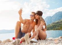 Συνεδρίαση ζεύγους σε μια παραλία και λήψη ενός selfie Στοκ φωτογραφία με δικαίωμα ελεύθερης χρήσης
