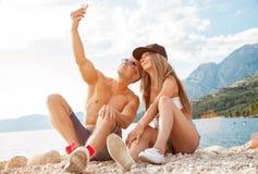 Συνεδρίαση ζεύγους σε μια παραλία και λήψη ενός selfie Στοκ εικόνες με δικαίωμα ελεύθερης χρήσης