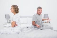 Συνεδρίαση ζεύγους στις διαφορετικές πλευρές του κρεβατιού που έχει μια διαφωνία στοκ εικόνα