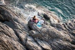 Συνεδρίαση ζεύγους στις κουβέρτες στους βράχους που κοιτάζουν έξω στη θάλασσα Στοκ Εικόνα