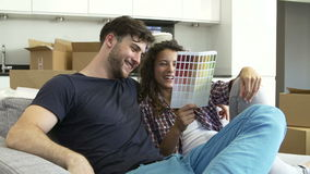Συνεδρίαση ζεύγους στον καναπέ που εξετάζει τα διαγράμματα χρωμάτων απόθεμα βίντεο