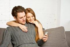 Συνεδρίαση ζεύγους στον καναπέ, που προσέχει κάτι στο κινητό τηλέφωνο Στοκ φωτογραφίες με δικαίωμα ελεύθερης χρήσης