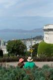 Συνεδρίαση ζεύγους στον πάγκο και κοίταγμα στο citysca του Σαν Φρανσίσκο Στοκ Εικόνες