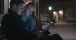 Συνεδρίαση ζεύγους στον πάγκο με την ταμπλέτα απόθεμα βίντεο