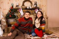 Συνεδρίαση ζεύγους στο πάτωμα μέσα στην καμπίνα κούτσουρων το χειμώνα Στοκ Φωτογραφία