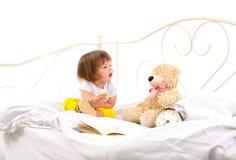 Συνεδρίαση κοριτσάκι στο άσπρο κρεβάτι στοκ εικόνα