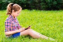 Συνεδρίαση κοριτσιών εφήβων στη χλόη με την ψηφιακή ταμπλέτα στα γόνατά της Στοκ φωτογραφία με δικαίωμα ελεύθερης χρήσης