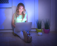 Συνεδρίαση κοριτσιών ομορφιάς σε ένα πάτωμα τη νύχτα και χρησιμοποιώντας το lap-top Στοκ εικόνα με δικαίωμα ελεύθερης χρήσης