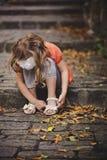 Συνεδρίαση κοριτσιών παιδιών στο δρόμο πετρών με τα βήματα στη θερμή ημέρα φθινοπώρου Στοκ Φωτογραφίες