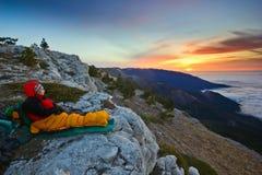 Συνεδρίαση κοριτσιών σε έναν απότομο βράχο στα βουνά στην ανατολή στοκ εικόνα