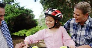 Συνεδρίαση κοριτσιών σε ένα ποδήλατο ενώ ευτυχείς γονείς που δίνουν υψηλά πέντε και αγκάλιασμα την φιλμ μικρού μήκους