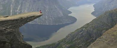 Συνεδρίαση κοριτσιών σε Trolltunga στη Νορβηγία στοκ φωτογραφία