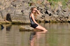 Συνεδρίαση κοριτσιών στη λίμνη Στοκ φωτογραφία με δικαίωμα ελεύθερης χρήσης