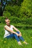 Συνεδρίαση κοριτσιών στη χλόη με την πικραλίδα στοκ φωτογραφία με δικαίωμα ελεύθερης χρήσης