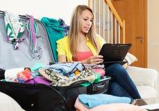 Συνεδρίαση κοριτσιών στον καναπέ κοντά στις αποσκευές Στοκ φωτογραφία με δικαίωμα ελεύθερης χρήσης