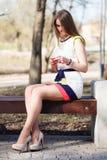 Συνεδρίαση κοριτσιών στον πάγκο με το κινητό τηλέφωνο στο πάρκο άνοιξη Στοκ φωτογραφίες με δικαίωμα ελεύθερης χρήσης