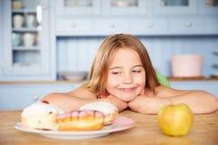 Συνεδρίαση κοριτσιών στον πίνακα που επιλέγει τα κέικ ή τη Apple για το πρόχειρο φαγητό Στοκ φωτογραφίες με δικαίωμα ελεύθερης χρήσης