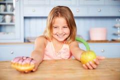Συνεδρίαση κοριτσιών στον πίνακα που επιλέγει τα κέικ ή τη Apple για το πρόχειρο φαγητό Στοκ εικόνες με δικαίωμα ελεύθερης χρήσης