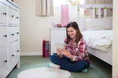 Συνεδρίαση κοριτσιών στο πάτωμα της κρεβατοκάμαρας που χρησιμοποιεί την ψηφιακή ταμπλέτα στοκ εικόνα