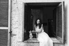 Συνεδρίαση κοριτσιών στο παράθυρο με τη γάτα Στοκ εικόνα με δικαίωμα ελεύθερης χρήσης