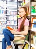Συνεδρίαση κοριτσιών χαμόγελου στην καρέκλα στη βιβλιοθήκη Στοκ Φωτογραφίες