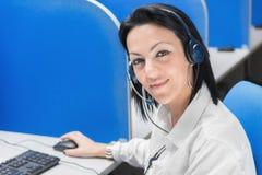 Συνεδρίαση κοριτσιών χειριστών τηλεφωνικών κέντρων χαμόγελου στο γραφείο με τον υπολογιστή Στοκ Εικόνα