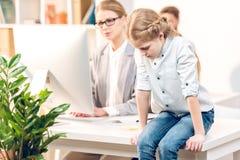 Συνεδρίαση κορών στον πίνακα, επιχειρηματίας που λειτουργεί με τον υπολογιστή πίσω από στην αρχή Στοκ φωτογραφία με δικαίωμα ελεύθερης χρήσης