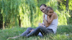 Συνεδρίαση μητέρων και κορών και αγκάλιασμα κατά κάνοντας την άσκηση γιόγκας στο πράσινο πάρκο απόθεμα βίντεο