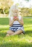 Συνεδρίαση μικρών κοριτσιών και κατανάλωση της Apple υπαίθρια Στοκ φωτογραφία με δικαίωμα ελεύθερης χρήσης