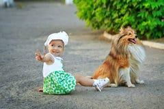 Συνεδρίαση μικρών κοριτσιών και σκυλιών στο έδαφος Στοκ φωτογραφία με δικαίωμα ελεύθερης χρήσης